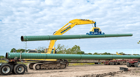 A large crane moves a piece of pipeline over a construction zone